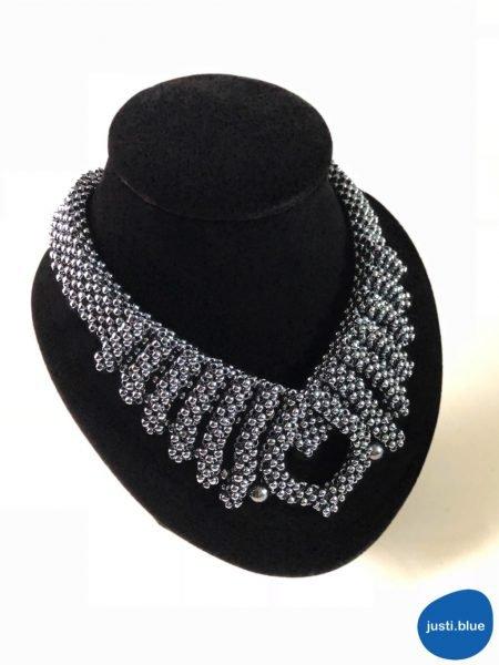 hematite necklace on black jewelry display